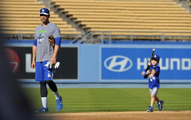 Los Angeles Dodgers' Andre Ethier walks of the field as his son Retton follows after practice in preparation for Game 3 of the National League baseball division series against the Atlanta Braves, Saturday, Oct. 5, 2013, in Los Angeles. (AP Photo/Mark J. Terrill)
