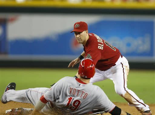 Arizona Diamondbacks shortstop Willie Bloomquist, top, tags out Cincinnati Reds Joey Votto (19) who wastrying to stretch a double in the fifth inning during a baseball game on Sunday, June 23, 2013, in Phoenix. (AP Photo/Rick Scuteri)