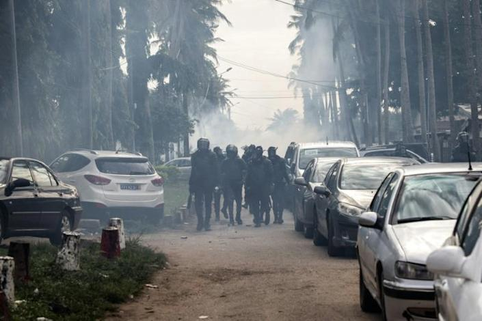 Tension: Riot police walk through a cloud of tear gas after dispersing a crowd of Gbagbo followers
