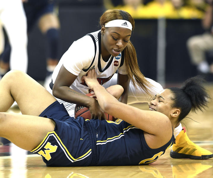 Louisville guard Dana Evans (1) battles Michigan forward Naz Hillmon (00) for a loose ball during the first half of a second-round game in the NCAA women's college basketball tournament in Louisville, Ky., Sunday, March 24, 2019. Louisville won 50-71. (AP Photo/Timothy D. Easley)