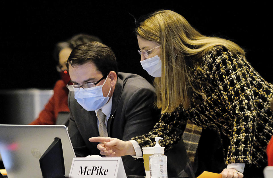 Sen. Jeremy McPike, D-Prince William, left, and Sen. Siobhan Dunnavant, R-Henrico, right, confer during the floor session of the Virginia Senate inside the Science Museum of Virginia in Richmond, Va., Monday, Feb. 1, 2021. (Bob Brown/Richmond Times-Dispatch via AP)