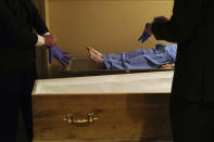 Pallbearers, Louis Mercier, right, and Allan Pottier, left, prepare to carry the body of a 105-year-old woman as they prepare her for funeral at a mortuary, in Paris, Friday, April 24, 2020, as a nationwide confinement continues to counter the COVID-19 virus. As body after body has passed through his rubber-gloved hands, sealed in double-layered bags for disposal, Paris undertaker Franck Vasseur has become increasingly concerned about the future after the coronavirus pandemic. All these people ferried in his hearse to cremations that their loved ones couldn't attend: when will they be mourned? (AP Photo/Francois Mori)
