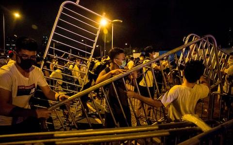 Protesters block roads with barricades during clashes with police - Credit: ISAAC LAWRENCE/AFP/Getty Images