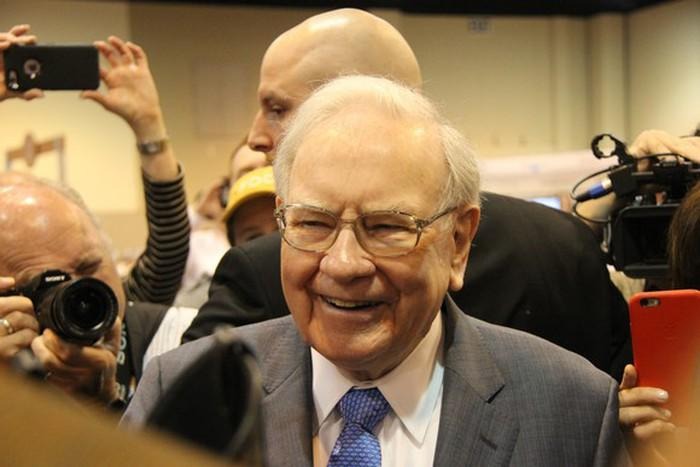 Warren Buffett with people behind him taking pictures of him