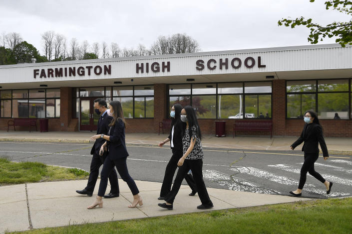 In this Monday, May 10, 2021 photo, Connecticut Attorney General William Tong left, walks with teacher Clarissa Tan, second from left, and students from the Asian American Student Union after speaking at a program for Asian Pacific American Heritage Month at Farmington High School in Farmington, Conn. The year of anti-Asian violence has led students and teachers to advocate for reexamining how Asian American studies and history are taught in public schools. (AP Photo/Jessica Hill)
