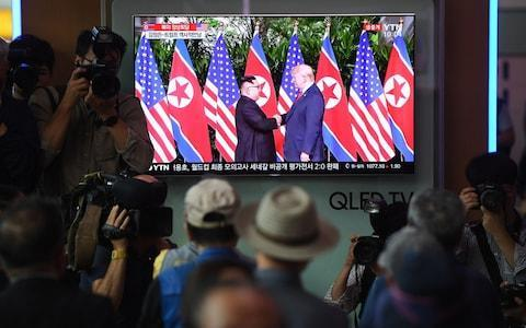 People watch a television screen showing live footage of the summit between US President Donald Trump and North Korean leader Kim Jong-un in Singapore, at a railway station in Seoul - Credit: Jung Yeon-je/AFP
