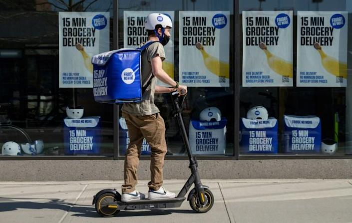 An employee rides a scooter to deliver groceries from 'Fridge No More' in Brooklyn