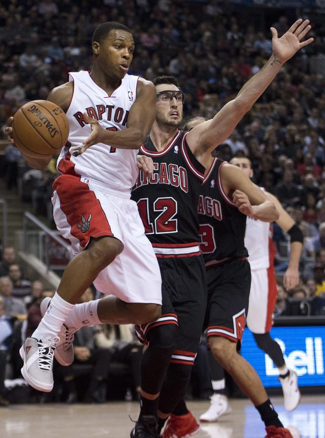 Toronto Raptors guard Kyle Lowry, left, drives past Chicago Bulls guard Kirk Hinrich, right, during first-half NBA basketball game action in Toronto, Friday, Nov. 15, 2013. (AP Photo/The Canadian Press, Nathan Denette)