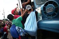 Honduran migrants, part of a caravan trying to reach the U.S., climb on a truck during a new leg of their travel in Zacapa, Guatemala October 17, 2018. REUTERS/Edgard Garrido