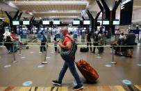 A passenger walks to the check-in counter at the O.R. Tambo International Airport in Johannesburg