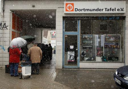 "FILE PHOTO: People line up during snow fall to receive food that is either to old or not looking nice enough for sale at the non-profit Dortmund food bank ""Dortmunder Tafel""  in the western German city of Dortmund March 20, 2013. REUTERS/Ina Fassbender/File Photo"