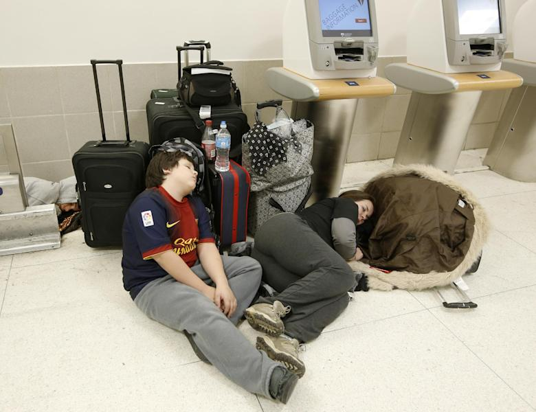 Evan, Ace, and Laura Peagels sleep on the floor in the baggage area of Delta Airlines Terminal 2 at Kennedy International Airport after a Delta flight from Toronto to New York skidded off the runway during icy conditions delaying all air traffic into and out of the airport, Sunday, Jan. 5, 2014, in New York. The family was vacationing in Mexico for a month and are trying to get the kids back to school. Peagel's father is driving four hours from New Jersey to pick them up and deliver them home. (AP Photo/Kathy Willens)