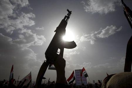 A Houthi follower rises a weapon as he attends a rally marking one year of Saudi-led air strikes, in Yemen's capital Sanaa, March 26, 2016. REUTERS/Mohamed al-Sayaghi/Files