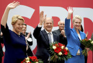 Front from left, Franziska Giffey, top candidate of the SPD for Mayor of the German city of Berlin, Olaf Scholz, top candidate for chancellor of the Social Democratic Party (SPD), and Manuela Schwesig, member of the SPD and governor of the German state of Mecklenburg-Western Pomerania, pose with flowers at the party's headquarter in Berlin, Germany, Monday, Sept. 27, 2021. The center-left Social Democrats have won the biggest share of the vote in Germany's national election. They narrowly beat outgoing Chancellor Angela Merkel's center-right Union bloc in a closely fought race that will determine who succeeds the long-time leader at the helm of Europe's biggest economy. (AP Photo/Michael Sohn)