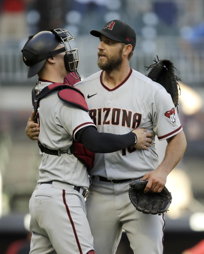 Arizona Diamondbacks pitcher Madison Bumgarner, right, is congratulated by catcher Carson Kelly after pitching a 7-inning no hitter against the Atlanta Braves, at the end of the second baseball game of a double header, Sunday, April 25, 2021, in Atlanta. (AP Photo/Ben Margot)