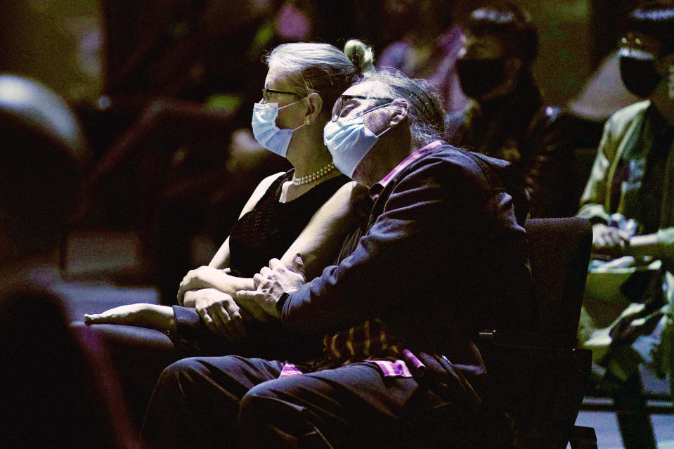 A man and woman listen to a concert by the New York Philharmonic, which performed before a live audience for the first time since March 10, 2020, at The Shed in Hudson Yards, Wednesday, April 14, 2021, in New York. (AP Photo/Kathy Willens)