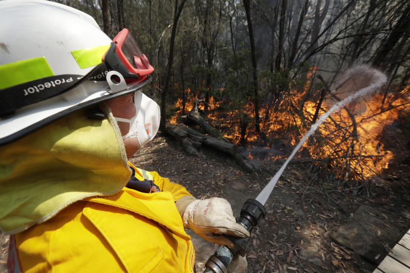 FILE - In this Dec. 8, 2019 file photo a firefighter controls a backburn near Mangrove Mountain, north of Sydney, Australia. U.S. officials said Tuesday, Jan. 7, 2020 they are planning to send at least 100 more firefighters to Australia to join 159 already there battling blazes that have killed multiple people and destroyed thousands of homes. (AP Photo/Rick Rycroft,File)