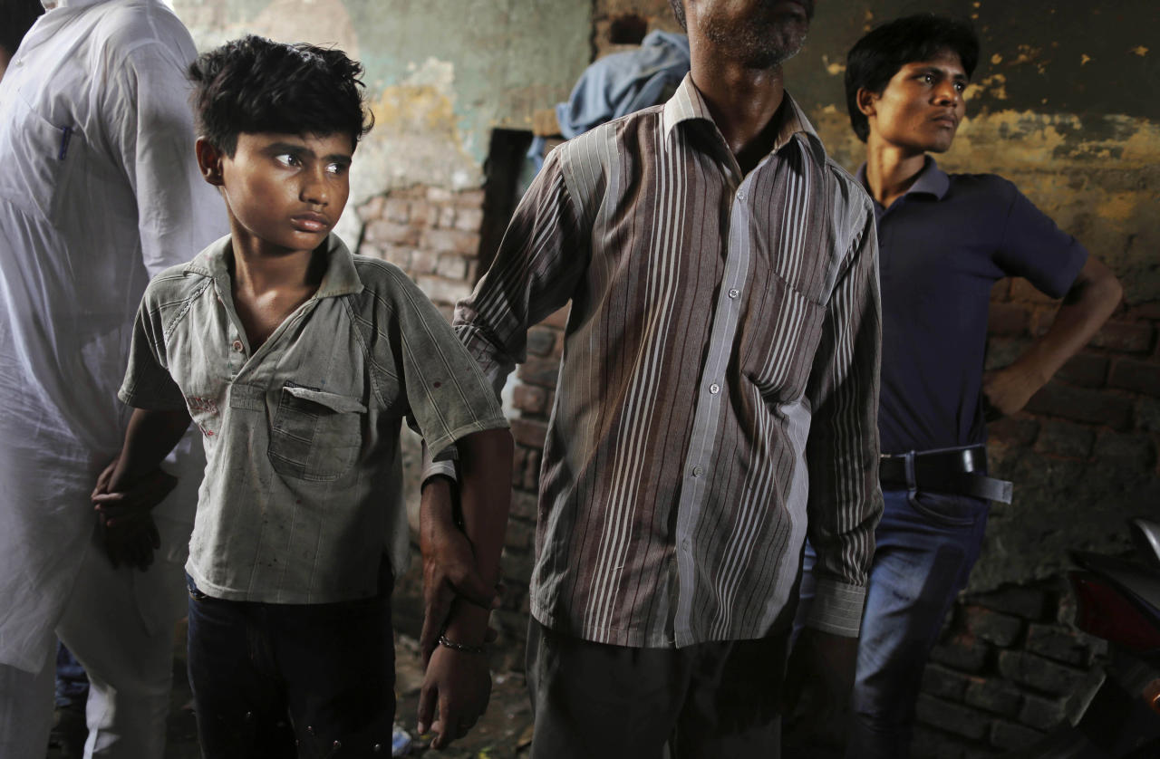 A young Indian bonded child laborer is walked away after being rescued during a raid by workers from Bachpan Bachao Andolan, or Save the Childhood Movement, at a factory in New Delhi, India, Tuesday, June 12, 2012. Raids on factories in the Indian capital revealed dozens of migrant kids hard at work Tuesday despite laws against child labor. Police rounded up 26 children from three textiles factories and a metal processing plant, but dozens more are believed to have escaped. Those captured had all come to New Delhi from the states of Bihar and Uttar Pradesh. (AP Photo/Kevin Frayer)