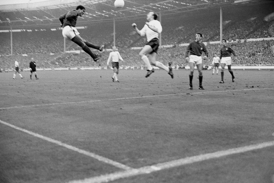 Eusebio of Portugal jumps with England's Nobby Stiles during the World Cup semi-final at Wembley, London. England won the match 2-1 (Photo by PA Images via Getty Images)