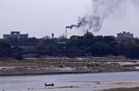 Men row a boat in the river Ganges as smoke emits from a chimney of a leather tannery at an industrial area in Kanpur, India, May 4, 2018. Picture taken May 4, 2018. REUTERS/Adnan Abidi