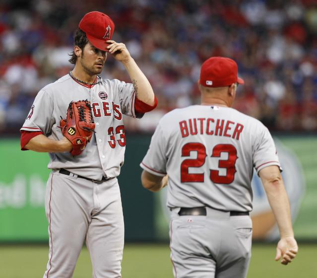 Los Angeles Angels pitching coach Mike Butcher (23) heads to the mound for a conference with starting pitcher C.J. Wilson (33) during the second inning of a baseball game against the Texas Rangers, Tuesday, July 30, 2013, in Arlington, Texas. (AP Photo/Jim Cowsert)