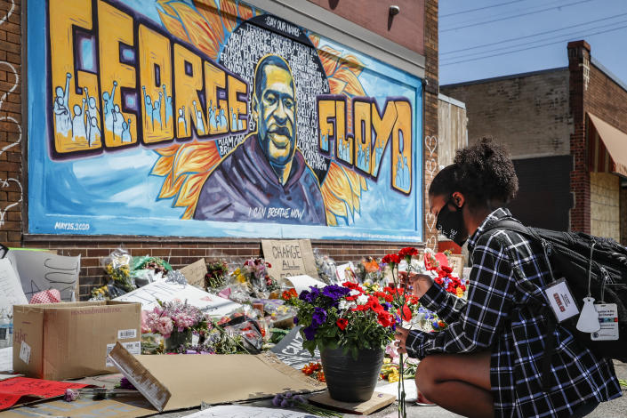 A woman places flowers at a memorial mural for George Floyd in Minneapolis on Sunday. (John Minchillo/AP)