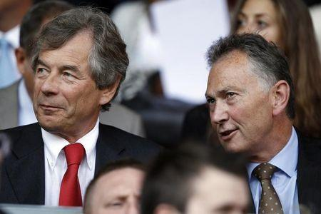 Liverpool's chairman Broughton sits with Premier League Chief Executive Scudamore before their English Premier League soccer match against Arsenal at Anfield in Liverpool