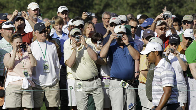 <p>Spectators take photos as Tiger Woods walks down the sixth fairway during a practice round for the Masters golf tournament in Augusta, Ga., Monday, April 5, 2010. The tournament begins Thursday, April, 8. (AP Photo/David J. Phillip) </p>