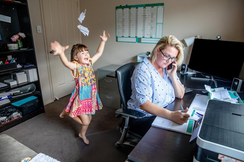 Mother attempts to work from home on the computer and phone whilst her daughter copies her, makes a mess and throws the laundry around.