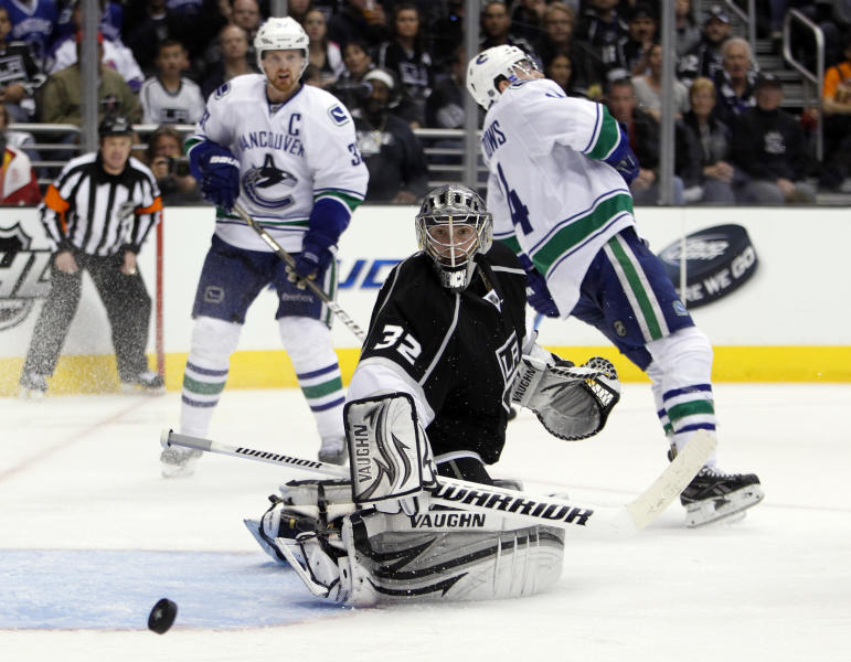 Los Angeles Kings goalie Jonathan Quick (32) deflects the puck away with Vancouver Canucks right wing Alex Burrows (14) losing an edge during the third period of Game 3 in a first-round NHL Stanley Cup playoff series in Los Angeles, Sunday, April 15, 2012. The Kings won the game 1-0. (AP Photo/Alex Gallardo)