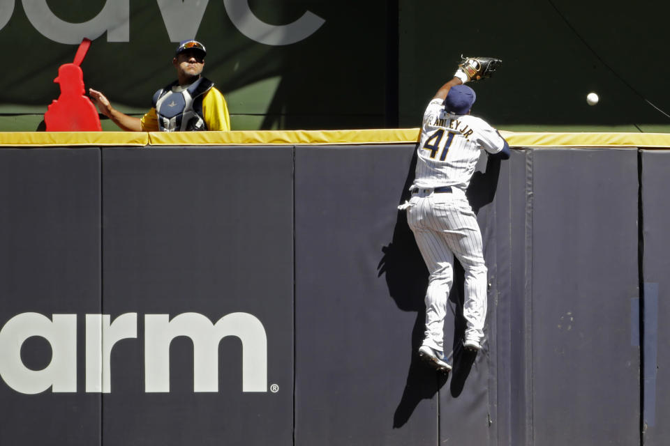 Milwaukee Brewers' Jackie Bradley Jr. is unable to make a catch at the wall on a solo home run hit by Pittsburgh Pirates' Jacob Stallings during the sixth inning of a baseball game Sunday, June 13, 2021, in Milwaukee. (AP Photo/Aaron Gash)