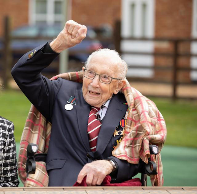 Captain Tom Moore waves to a Battle of Britain Memorial Flight flypast of a Spitfire and a Hurricane passing over his home as he celebrates his 100th birthday. (PA)