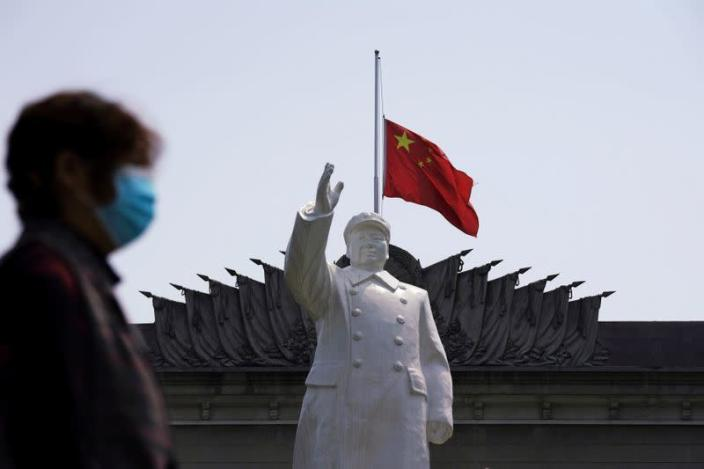 FILE PHOTO: FILE PHOTO: The Chinese national flag flies at half-mast behind a statue of late Chinese chairman Mao Zedong in Wuhan