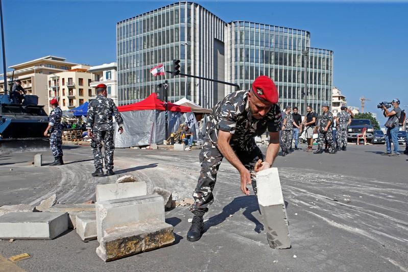 A lebanese police removes a concrete block used by demonstrators to block a highway in Beirut