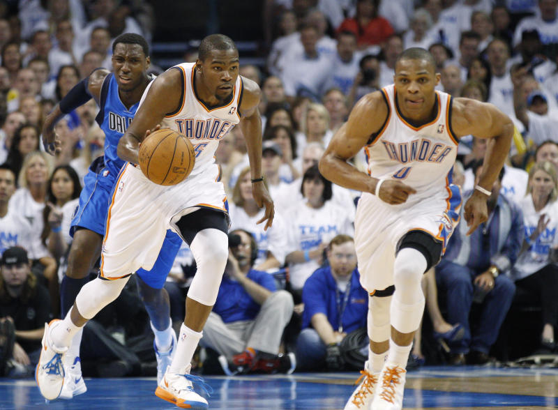 Oklahoma City Thunder forward Kevin Durant, center, heads upcourt with teammate Russell Westbrook, right, and Dallas Mavericks center Ian Mahinmi, left, in the second quarter of Game 2 in the first round of the NBA basketball playoffs, in Oklahoma City, Monday, April 30, 2012. (AP Photo/Sue Ogrocki)