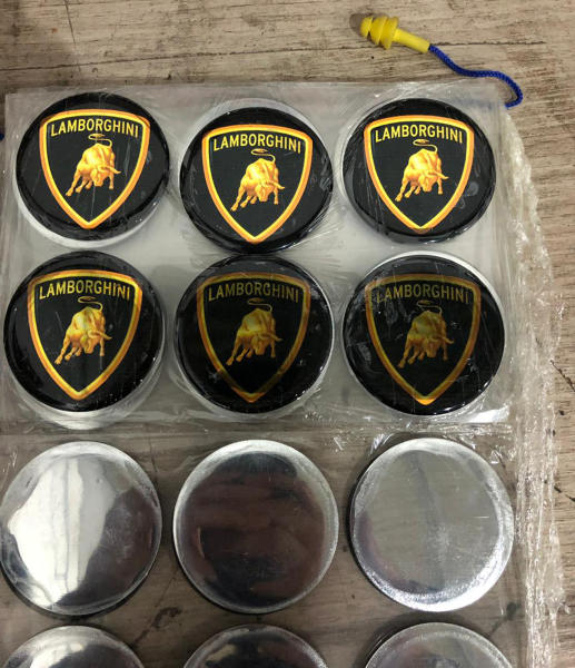 This July 15, 2019 photo released by Itajai Civil Police shows emblem badges stamped with the Lamborghini logo, inside a workshop in Itajai, Brazil. Brazilian police dismantled the clandestine workshop run by a father and son who assembled fake Ferraris and Lamborghinis, in Brazil's southern state of Santa Catarina. (Itajai Civil Police via AP) (Itajai Civil Police via AP)