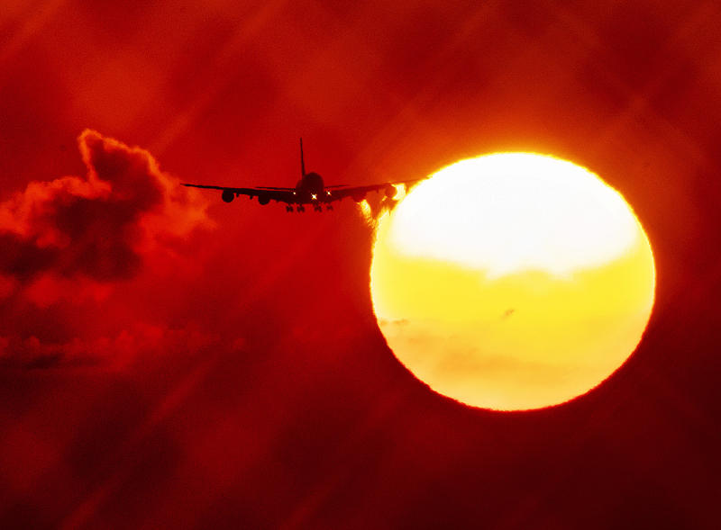 FILE - In this Wednesday, Aug. 21, 2019 file photo, an aircraft passes the rising sun as it approaches the airport in Frankfurt, Germany. The European Union says it will miss its targets for reducing planet-warming greenhouse gases by 2030 unless member states make a greater effort than they have so far. (AP Photo/Michael Probst, File)