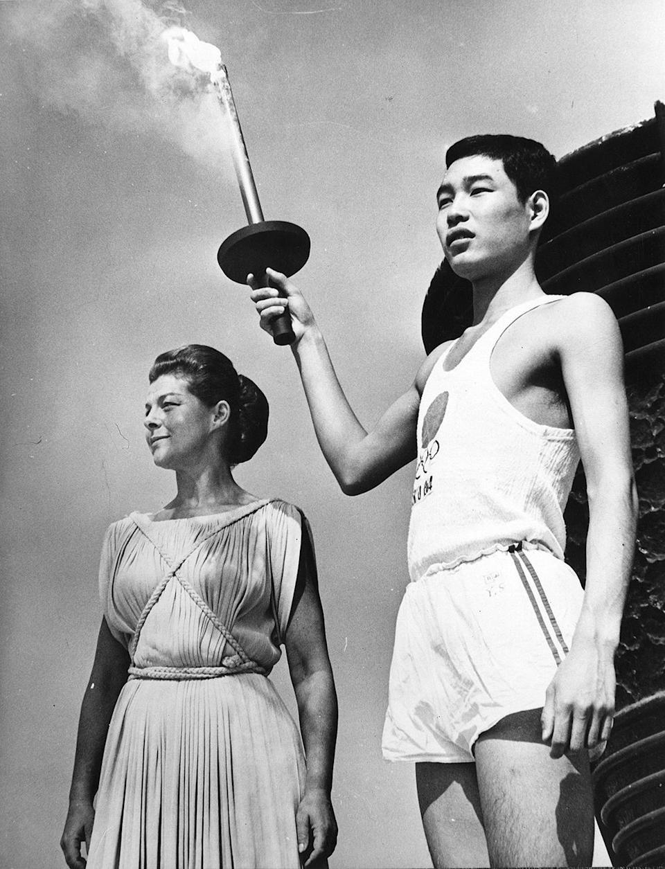 <p>Sakai, who was born in Hiroshima on the day the first atomic bomb was dropped on the city, holds the Olympic torch next to Greek actress Aleka Katselli during a rehearsal for the opening of the Olympic Games.</p>