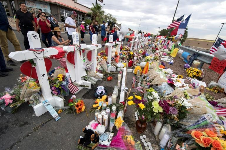 People leave flowers at a makeshift memorial for shooting victims at the El Paso Walmart in August 2019