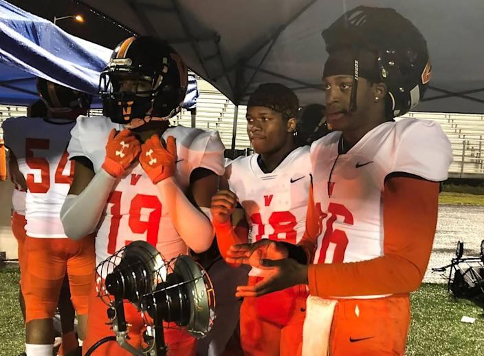 Members of the Vance Cougars football team huddle under a tent with portable heaters during their 27-7 win over Mallard Creek Friday night.
