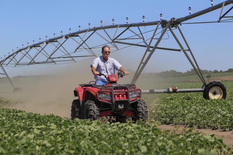 In this Friday, June 28, 2013 photo, Jim Carlson drives an ATV through a field of soybeans after shutting off the water in his central pivot irrigator in Silver Creek, north of Osceola, Neb. The route of the proposed Keystone XL pipeline runs through this field. Carlson supports turning to county officials and zoning boards to approve resolutions formally opposing the pipeline, in hopes of a symbolic win to show the federal government that the project has local opposition. (AP Photo/Nati Harnik)