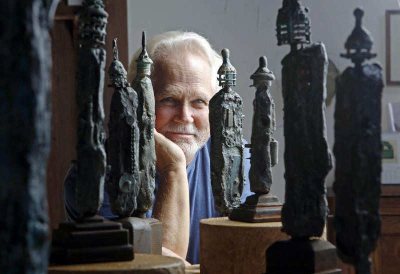 """In this Thursday, Sept. 18, 2012 photo, Tony Dow, actor, director and artist, poses with some of his works at his home and studio in the Topanga area of Los Angeles. When it comes time to sitting down in a studio and carving out bronze and wooden sculptures inspired by the nature all around him, Wally isn't leaving it up to the Beav these days. Dow, who famously played the Beaver's older brother Wally on the classic 1950s-60s sitcom """"Leave it To Beaver,"""" is carving out a name for himself in the art world these days, as an abstract artist. (AP Photo/Reed Saxon)"""