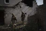 FILE - In this Tuesday, May 4, 2021 file photo, Ukrainian soldiers walk next to a destroyed house near a fighting position on the line of separation from pro-Russian rebels near Donetsk, Ukraine. Soldiers anxiety is high amid an increase in attacks this year. After a long period of tense quiet last year, 34 soldiers have been killed this year by firing from the separatists. (AP Photo/Felipe Dana, File)