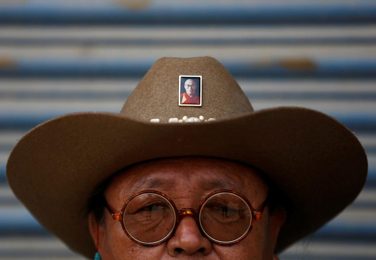 "A Tibetan man wears a hat with a portrait of exiled Tibetan spiritual leader, the Dalai Lama, during a function organised to mark ""Losar"" or the Tibetan New Year at a Tibetan Refugee Camp in Lalitpur, Nepal February 16, 2018. REUTERS/Navesh Chitrakar"