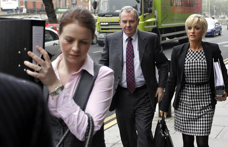 FILE This , Friday, Oct. 19, 2012 file photo shows Sean Quinn, center, arriving at the High court with his daughter-in-law Karen Woods, right, in Dublin, Ireland. A judge in Ireland on Friday Nov. 2, 2012 ordered bankrupt tycoon Sean Quinn jailed for nine weeks for failing to observe orders to stop placing foreign property assets beyond the reach of creditors. Quinn — Ireland's richest man until 2008 — faces financial ruin because of his reckless gamble that year on Anglo Irish Bank. The Dublin lender was the biggest financier of Ireland's runaway property market, a boom that imploded in 2009. (AP Photo/Peter Morrison)