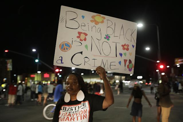 A woman holds up a sign during a demonstration in reaction to the acquittal of neighborhood watch volunteer George Zimmerman on Monday, July 15, 2013, in Los Angeles. Anger over the acquittal of a U.S. neighborhood watch volunteer who shot dead an unarmed black teenager continued Monday, with civil rights leaders saying mostly peaceful protests will continue this weekend with vigils in dozens of cities. (AP Photo/Jae C. Hong)