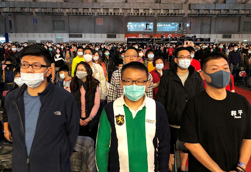 FILE PHOTO: Foxconn employees wearing masks attend the company's year-end gala in Taipei, Taiwan January 22, 2020. REUTERS/Yimou Lee/File Photo