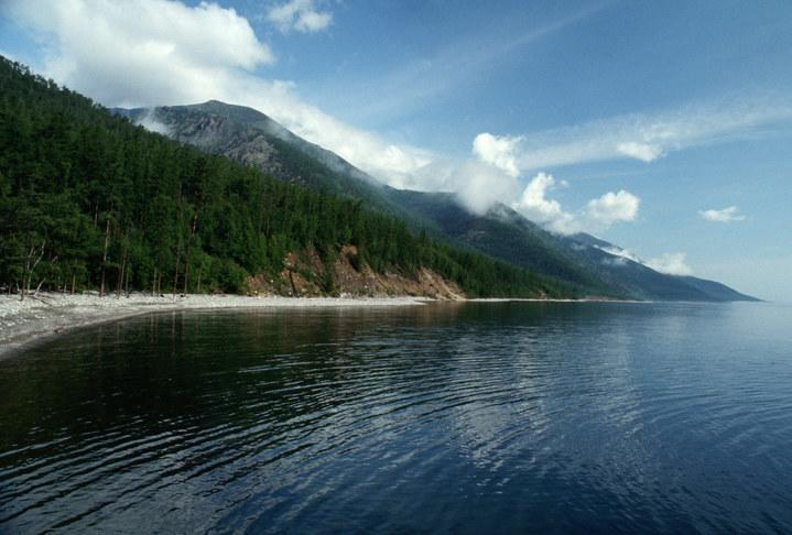 The shoreline and water of Lake Baikal with misty mountains in the distance