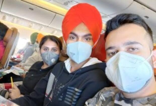 Sandeep Kathuria is pictured here on the far right on the flight from India to Canada.