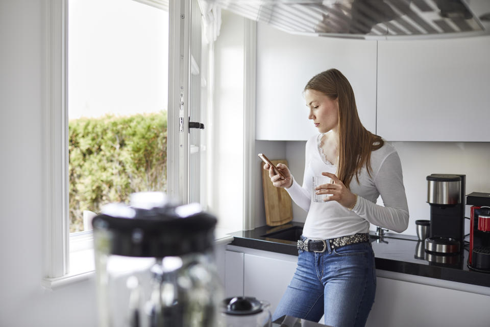 Young woman using cell phone in kitchen